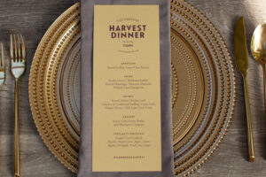 Gold, grey and purple place setting with menu atop gold charger